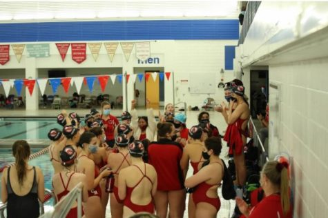 Coon Rapids Girls swim and dive team sport their masks on the pool deck after winning their second to the last meet against the Osseo Orioles.